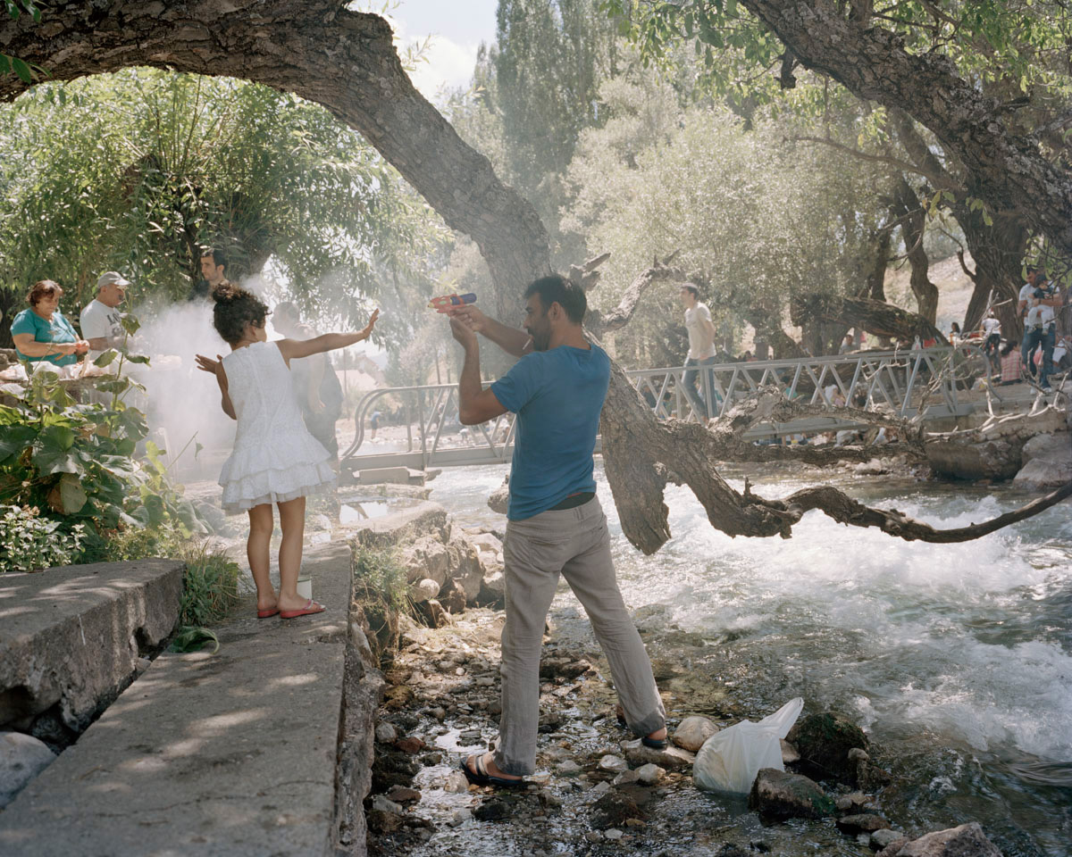A father plays with his daughter at a family picknick by the holy Munzur Springs